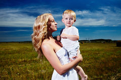 Enfant et jeune femme avec des fleurs jouant dans le domaine la fleur de jour donne à des mères le fils de momie à Images stock