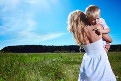 Enfant et jeune femme avec des fleurs jouant dans le domaine la fleur de jour donne à des mères le fils de momie à Photos stock