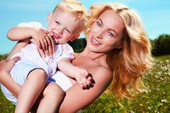 Enfant et jeune femme avec des fleurs jouant dans le domaine la fleur de jour donne à des mères le fils de momie à Photo stock