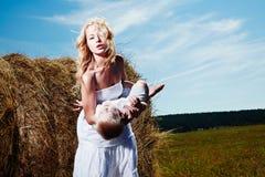 Enfant et jeune femme avec des fleurs jouant dans le domaine la fleur de jour donne à des mères le fils de momie à Images libres de droits