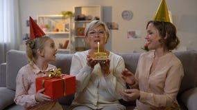 Enfant et mère féminins dans donner de chapeaux de partie actuel, célébrant l'anniversaire de mamie clips vidéos