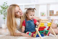 Enfant et mère jouant avec l'abaque Images libres de droits