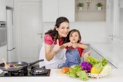 Enfant et mère montrant la cuisine CORRECTE de connexion Images stock