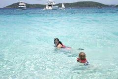 Enfant et mère naviguant au schnorchel dans l'océan tropical Images libres de droits