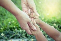 Enfant et mère tenant la main ainsi que l'amour en parc Photo stock