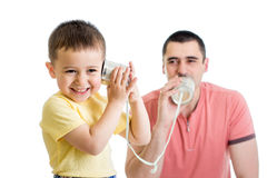 Enfant et papa ayant un appel téléphonique avec les boîtes en fer blanc Photos libres de droits