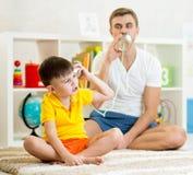 Enfant et papa ayant un appel téléphonique avec les boîtes en fer blanc photo stock