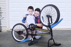 Enfant et papa réparant la bicyclette cassée Image stock