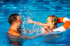 Enfant et père jouant dans la piscine Images libres de droits