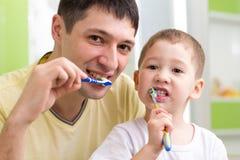 Enfant et ses dents de brossage de père dans la salle de bains Image libre de droits