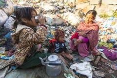 Enfant et ses parents pendant le déjeuner dans la coupure entre travailler à la décharge Image libre de droits
