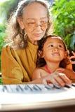 Enfant ethnique et grand-mère jouant le piano Photographie stock