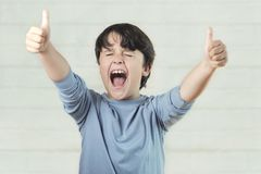 Enfant euphorique montrant des pouces  photographie stock