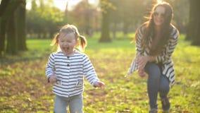 Enfant féminin actif ayant l'amusement pendant le Sunny Spring Day La petite fille drôle court à partir de son jouer de mère clips vidéos