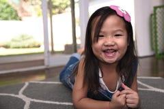 Enfant féminin asiatique se trouvant sur le plancher et le sourire Photos libres de droits