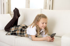 Enfant féminin avec les cheveux blonds se trouvant sur le sofa à la maison utilisant l'Internet APP au téléphone portable photographie stock