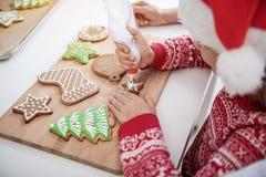 Enfant féminin concentré serrant la crème sur la pâtisserie de Noël photos stock
