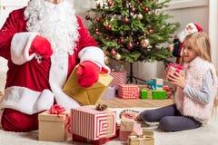 Enfant féminin curieux ayant des cadeaux de Noël Image libre de droits