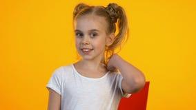 Enfant féminin heureux avec le sac à provisions clignant de l'oeil et souriant sur la caméra, bonnes remises clips vidéos