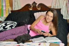 Enfant féminin mignon étudiant sur le lit avec son chien Photo stock