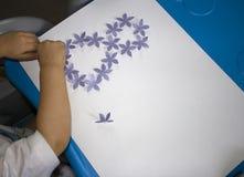 Enfant faisant la carte postale avec image le 8 mars Écritures d'enfant Matériel pour la créativité kindergarten photographie stock