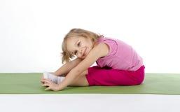 Enfant faisant la gymnastique sur un tapis Image libre de droits