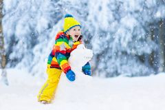 Enfant faisant le bonhomme de neige Jeu d'enfants dans la neige en hiver photo libre de droits