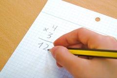 Enfant faisant une multiplication de maths comme devoirs Image stock