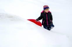 Enfant froid marchant dans la neige avec le traîneau Photo stock