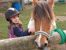 Enfant frottant le poney photographie stock