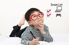 Enfant futé se trouvant sur le lit pensant la liste rêveuse Photographie stock libre de droits
