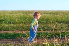Enfant gai dans la combinaison de jeans outre vers le bas de la route Photo stock