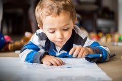 Enfant gai heureux dessinant à la maison Concept de créativité images stock