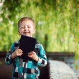 Enfant gai, heureux, souriant avec le comprimé dans des mains en parc Photos stock