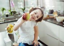 Enfant gai tenant une pomme, tir de cuisine Images stock