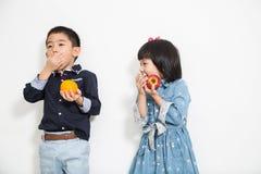 Enfant, garçon et fille de l'Asie mangeant du fruit Photo libre de droits