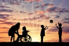 Enfant handicapé dans pleurer et le sien de fauteuil roulant mère près de jeu d'enfants avec la boule Images stock