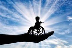 Enfant handicapé dans un fauteuil roulant dans la main d'un homme Photo libre de droits
