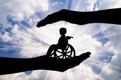 Enfant handicapé dans un fauteuil roulant dans les mains de l'homme Image stock