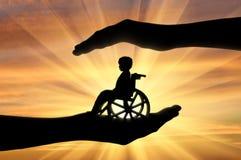Enfant handicapé dans un fauteuil roulant dans les mains de l'homme Photographie stock libre de droits