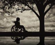 Enfant handicapé dans un fauteuil roulant pleurant près de l'arbre sur la plage Photos libres de droits