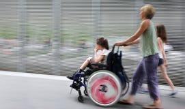 Enfant handicapé dans un fauteuil roulant sur une rue de ville Photos libres de droits