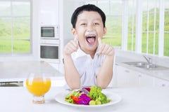 Enfant heureux avec de la salade et le jus photo libre de droits