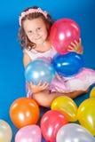 Enfant heureux avec des ballons colorés d'air au-dessus de bleu Photographie stock libre de droits