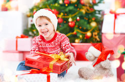 Enfant heureux avec des cadeaux de Noël près d'un arbre de Noël Images stock