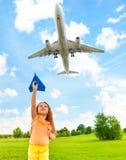 Enfant heureux avec l'avion de papier Photo stock
