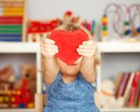 Enfant heureux avec le coeur de papier rouge Photo stock