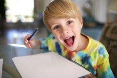 Enfant heureux avec le grand dessin de sourire sur le livre blanc avec le stylo Images stock