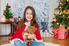 Enfant heureux avec le jouet se reposant devant l'arbre de Noël Photos stock
