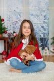 Enfant heureux avec le jouet se reposant devant l'arbre de Noël Images stock